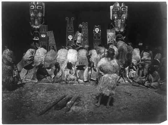 Kwakiutl-people-some-bowing-before-totem-poles-in-background-others-seated-facing-front-as-part-of-the-nunhlim-ceremony-the-four-days-prior-to-the-Winter-Dance